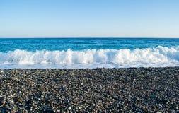 Die Wellen, die auf einem steinigen Strand brechen, bildend sprüht Stockfoto