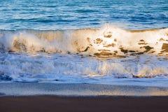 Die Wellen, die über Strand sich waschen, stützen mit warmem Morgensonnenlicht unter lizenzfreie stockfotos