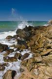 Die Wellen, die auf dem Strand mit Felsen spritzen stockfotografie