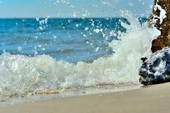 Die Wellen, die auf einem steinigen Strand brechen, Stockbilder