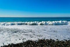 Die Wellen, die auf einem steinigen Strand brechen, bildend sprüht Stockbild