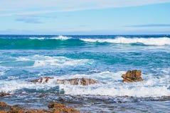 Die Wellen, die auf Felsen, perfektem Blau und Aquaozean zusammenstoßen, wässern, Felsen am Ufer, Altostratuswolken im Himmel Lizenzfreie Stockbilder