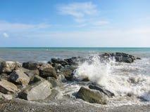 Die Wellen stoßen mit einem Spray von Felsen zusammen Stockfoto