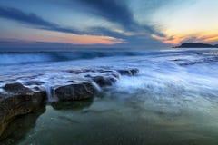 Die Wellen, welche die Felsen bei Alanya schlagen, setzt während des Sonnenuntergangs auf den Strand stockbild