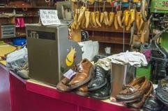 Die Werkstatt eines Schusters mit der repariert zu werden Ausrüstung und Schuhen stockbilder