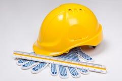 Die Werkzeuge des Erbauers - Sturzhelm, Arbeitshandschuhe und Machthaber über Weiß Lizenzfreies Stockbild