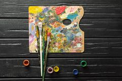 Die Werkzeuge des Künstlers, der Bürsten, der Farben und dunklen hölzernen des Hintergrundes der Palette nicht stockfotografie