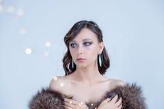 Die Winterfrau träumen, die oben schaut und Pelzhut tragend Modeporträt des schönen sexy Frauenmodells mit kreativem machen stockbilder