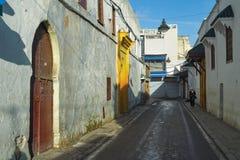 Die Wände der alten Stadt und der Frau, gekleidet in der arabischen nationalen Kleidung, gehend durch die alten Straßen der Stadt Lizenzfreie Stockfotografie