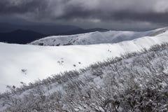 Die Wolke, die über Schnee auftaucht, bedeckte Berge Lizenzfreies Stockfoto