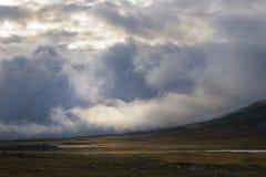 Die Wolken, die vorbei überschreiten und das Sonnenlicht überschreitet einmal durch die Wolken und das Beleuchten herauf die Herb Lizenzfreie Stockfotografie