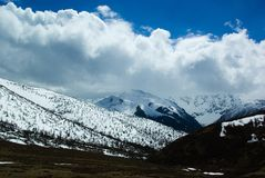 Die Wolkengruppe von schneebedeckten Bergen Stockfotos