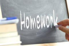 Die Wort Hausarbeithand geschrieben auf eine Tafel Lizenzfreies Stockbild