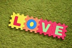 Die Wortliebe geschrieben mit einem Puzzlespiel der bunte Kinder stockfotos