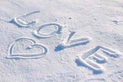 Die Wortliebe und ein Herz gezeichnet in den Schnee Lizenzfreie Stockfotografie