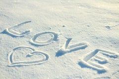 Die Wortliebe und ein Herz gezeichnet in den Schnee Stockfotografie