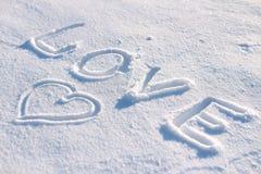 Die Wortliebe und ein Herz gezeichnet in den Schnee Stockbilder