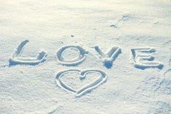 Die Wortliebe und ein Herz gezeichnet in den Schnee Stockfoto