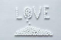 Die Wortliebe wird von den weißen Herzen auf einen weißen Hintergrund gezeichnet oder geschrieben Design mit Kopienraum Beschneid stockbild