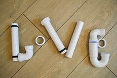 Die Wortliebe wird von der Klempnerarbeit, von den weißen Kunststoffrohren der Klempnerarbeit, von den Installationen, von den Fl Lizenzfreies Stockbild