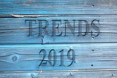 Die Worttendenzen und die Nr. 2019 auf einer hölzernen blauen Oberfläche lizenzfreie stockfotografie