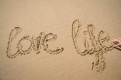 Die Wörter lieben das Leben, das in den Sand geschrieben wird Lizenzfreies Stockbild