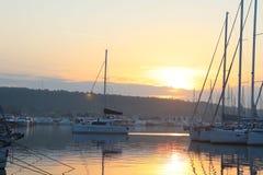 Die Yacht bringt von der Reise zum Jachthafen während der Morgendämmerungs-Segelnvergangenheit die festgemachten Segeljachten zur stockfoto
