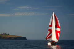 Die Yacht mit einem roten Segel nahe Insel. Stockbild
