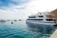 Die Yacht mit Touristen ist naher Pier im Hafen Stockbilder