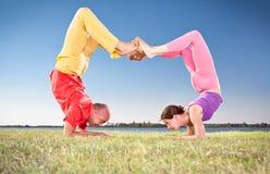 Die Yogapaare, -mann und -frau, die Vrschikasana Skorpion tun, werfen auf Stockbild