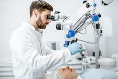 Die Zähne des Untersuchungspatienten des Zahnarztes mit einem Mikroskop stockfoto