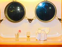 Die Zahl des Tuches gegen zwei Fenster in der Kabine ein Kreuzschiff Stockfotos