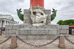 Die Zahl einer Frau, die am Fuß der Podiumsspalte auf dem Spucken von Vasilievsky-Insel sitzt Stockfoto