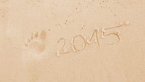 Die Zahl im Jahre 2015 und Abdruck im Sand Lizenzfreie Stockfotos