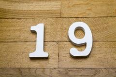 Die Zahl ist neunzehn auf einem hölzernen, Parkettboden lizenzfreie stockfotos