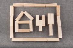 Die Zahlen, die von den hölzernen Ziegelsteinen des Spielzeugs gemacht wurden, lagen auf grauem Gewebehintergrund Lizenzfreie Stockfotos