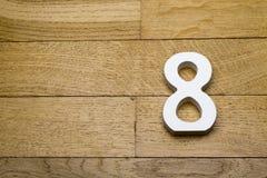 Die Zahlen sind acht auf dem hölzernen, Parkettboden Stockfotografie