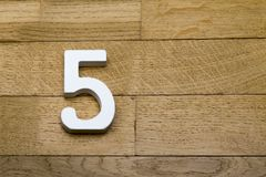 Die Zahlen sind fünf auf dem hölzernen, Parkettboden Lizenzfreie Stockfotografie