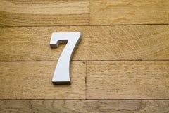 Die Zahlen sind sieben auf dem hölzernen, Parkettboden Stockfotografie