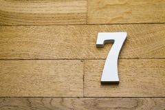 Die Zahlen sind sieben auf dem hölzernen, Parkettboden Lizenzfreies Stockbild
