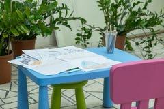 Die Zeichnungen der Kinder im Bleistift auf einer Tabelle Stockbilder