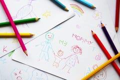 Die Zeichnungen und die farbigen Bleistifte des Kindes Lizenzfreies Stockbild