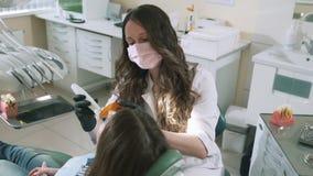 Die Zeitlupe, die einen weiblichen Zahnarzt schießt, arbeitet mit dem Gerät photopolymerizer, um sich zu verfestigen das Füllmate stock footage