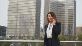 Die Zeitlupejournalistfrau in der Geschäftskleidung sprechend auf Smartphone gehen zu arbeiten stock video footage