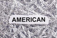 Die zerrissene Nahaufnahme bessert und Bänder des Papiers mit dem Wort AMERIKANER aus Stockfoto