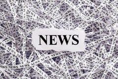 Die zerrissene Nahaufnahme bessert und Bänder des Papiers mit dem Wort NACHRICHTEN aus Stockfoto