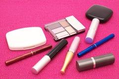 Die zerstreuten Kosmetik auf einem rosa Hintergrund Stockfotos