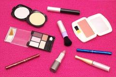 Die zerstreuten Kosmetik auf einem rosa Hintergrund Lizenzfreies Stockbild