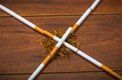 Die Zigaretten, die auf der Holzoberfläche formt in gekreuzte Linien liegen, Tabak verbreiteten herum, gesehen von oben Lizenzfreies Stockfoto