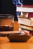 Die Zigarre schaltete sich, das Getränk und ein Stapel Bücher an Lizenzfreie Stockfotografie